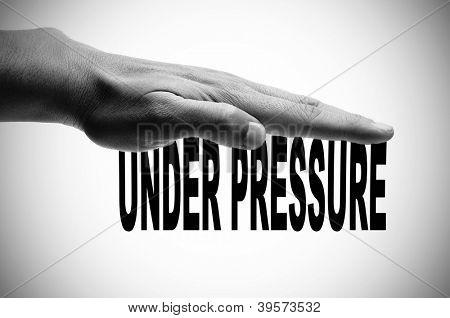 una mano de hombre en blanco y negro presionando la oración bajo presión escrita en negro