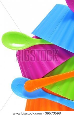 plastic bowls and spoons of different colors on a white background