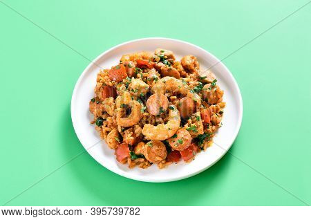 Creole Jambalaya With Chicken, Smoked Sausages And Vegetables On Plate Over Green Background With Co