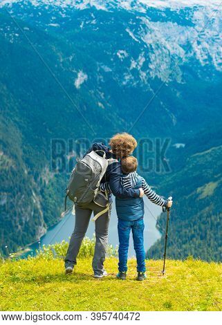 The boy and his mother with backpacks are standing on the top of the mountain.Mother and son tourist traveling and looking at the mountains. Hike and climb with kids.