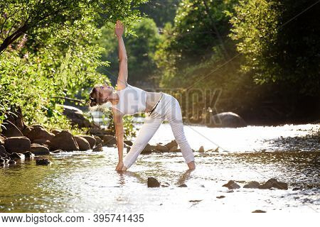 Young And Sexy Girl Practicing Yoga At The Evening Stream River. The Triangle Pose Of Yoga - Trikona