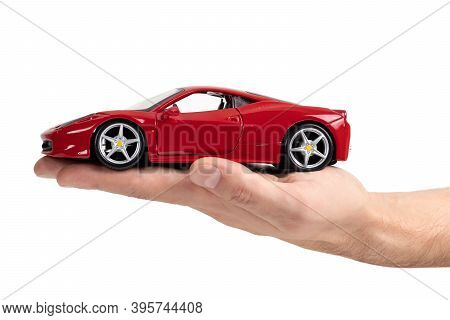 Ukraine. Dnipro. 15 November 2020. Model Of A Red Sports Car Ferrari In Hand On A White Background.