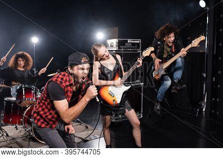 Kyiv, Ukraine - August 25, 2020: Vocalist Shouting In Microphone Leaning Forward Near Guitarist Jump