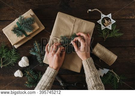 Christmas Wrapping Idea, Xmas Wrapping Workspace. Female Hands Wrap Gift Box In Kraft Recycled Paper