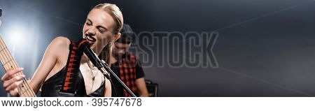 Rock Band Vocalist With Electric Guitar Singing In Microphone With Backlit And Blurred Man On Backgr