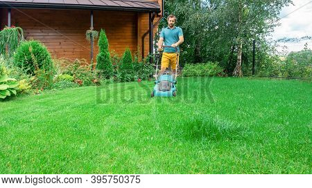 A Man Takes Care Of The Lawn With A Lawn Mower. Regular Mowing Of The Grass In The Summer Season. A