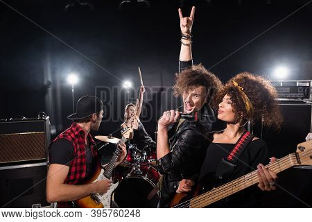 Kyiv, Ukraine - August 25, 2020: Excited Vocalist With Rock Gesture Holding Microphone Near Woman Wi