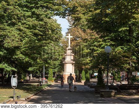 Pancevo, Serbia - September 26, 2020: People Passing By The Calvary And Catholic Cross Of The Trg Kr