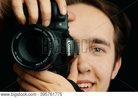 Smiling Man Takes Pictures On Canon Camera And Tries To Focus The Lens And Takes Pictures. Photo Edi