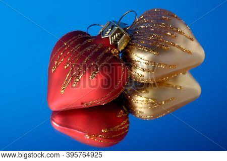 Two heart-shaped Christmas decoration ornaments on blue background