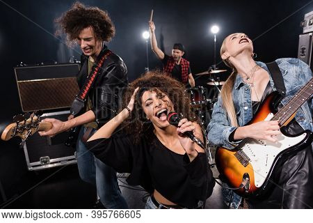 Kyiv, Ukraine - August 25, 2020: Female Singer Of Rock Band With Microphone Singing Near Guitarists
