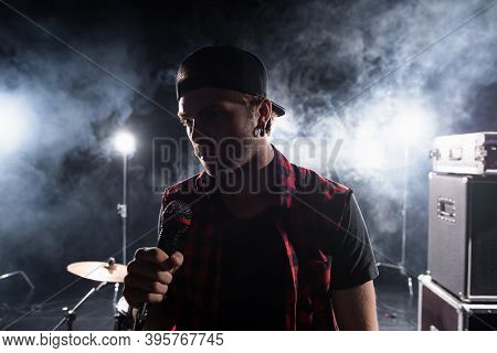 Rock Band Vocalist Holding Microphone, With Smoke And Backlit On Blurred