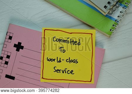 Commited To World-class Service Write On Sticky Note Isolated On Wooden Table.