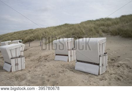 Images Shows Some Roofed Wicker Chairs On The Beach