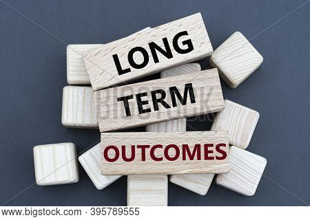 Long Term Outcomes - Words On Wooden Bars On Cubes On A Gray Background. Business And Finance Concep