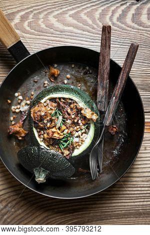 Vegetarian chanterelle stuffed round zucchini on wooden table