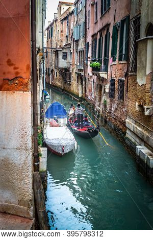 Gondolier In A Narrow Canal In World Famous Venice, Italy