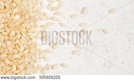 White Sesame - Sesamum Indicum - Seeds On White Stone Like Board, View From Above