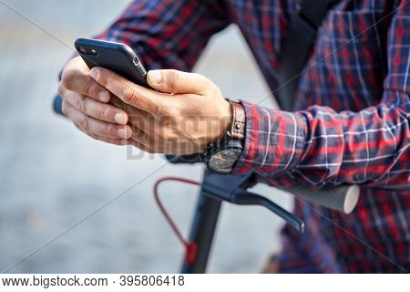 Young Man Wearing Shirt Leaning On Electric Scooter Handlebar, Holding Mobile Smartphone In His Hand