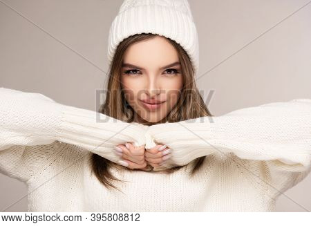 Trendy Warm Winter - Beautiful  Young Blonde  Woman In White Wool Winter Hat And  Knitted Sweater .