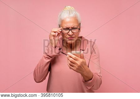 Confused Senior Woman With Wrinkles Is Using Her Smartphone Sending A Messag