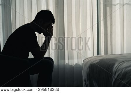 Silhouette Depressed Man Sadly Sitting On The Bed In The Bedroom, Depression Concept