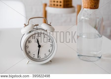 Alarm Clock And Glass Bottle With Water On The Table. Time To Drink Some Water. Daily Habits. Good H