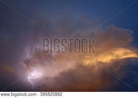 Storm Clouds And Lightening In The Evening Light
