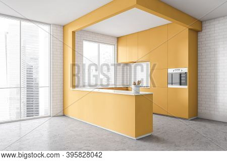 Corner Of Modern Kitchen With White Walls, Concrete Floor And Yellow Cupboards. Window With Blurry C