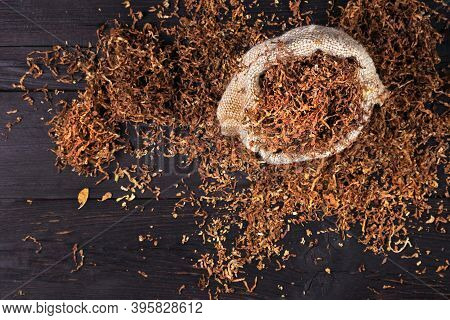 Dry Cut Tobacco Leaf On A Wooden Table. Tobacco In A Bag