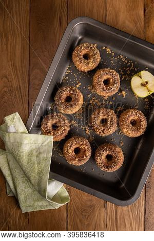 Baked Apple Cider Donuts With Apple Ingredient And Textile Napkin On Baking Tray On Natural Wooden T