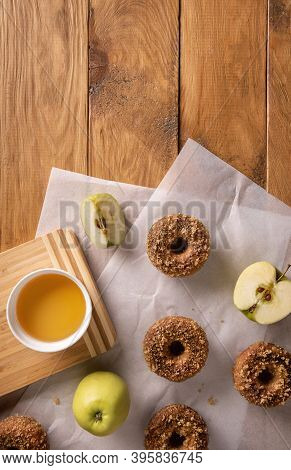 Baked Apple Cider Donuts With Apple Cider And Fruits On Baking Sheets On Natural Wooden Table. Ready
