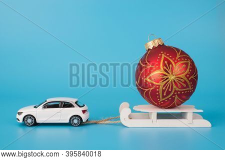 Christmas Preparations Concept. Close Up Photo Of Toy Mini Car Carrying White Wooden Sledge With Red