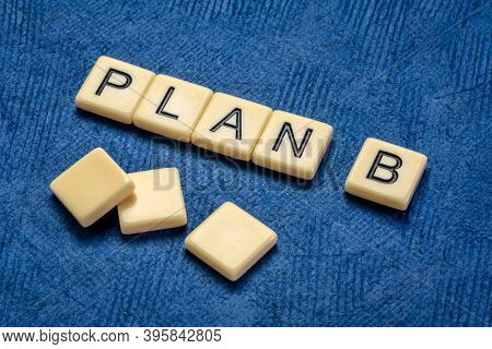 plan B text in ivory letter tiles against textured handmade paper, revision and changing business or personal plans and goals concept