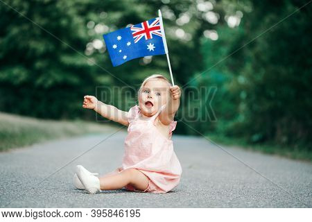 Cute Adorable Caucasian Baby Girl Waving Australian Flag. Smiling Child Sitting On Street Road In Pa