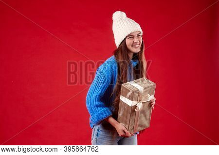 Girl In A Blue Sweater And White Hat Holding A Gift In Her Hands On A Red Background.