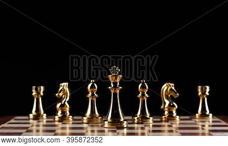 Golden Chess Figures Standing On Chessboard. Intellectual Competition And Fight In Business. Strateg