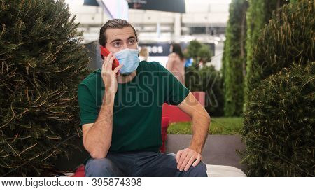 Young Man In Mask Makes Phone Call. Media. Man Observes Mask Regime In Public Place During Pandemic.