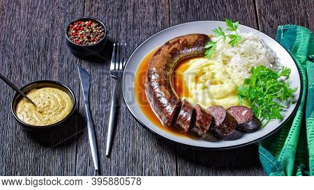 German Food: Blutwurst Or Blood Sausage Served On A Plate With Sauerkraut, Mashed Potato Parsley, Mu