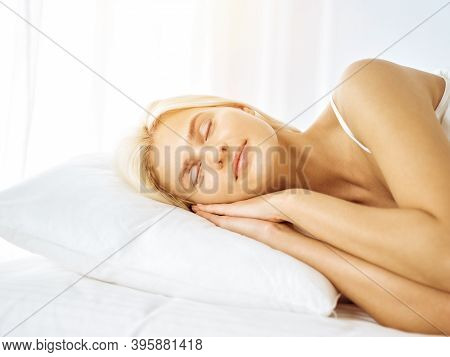 Beautiful Young Woman Sleeping While Lying In Bed Comfortably And Blissfully In Sunny Bedroom. Good