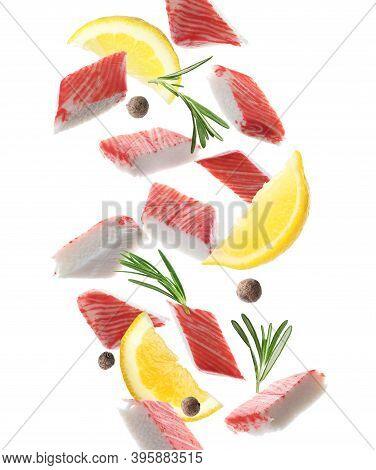 Cut Fresh Crab Sticks, Lemon, Rosemary And Allspice Falling On White Background