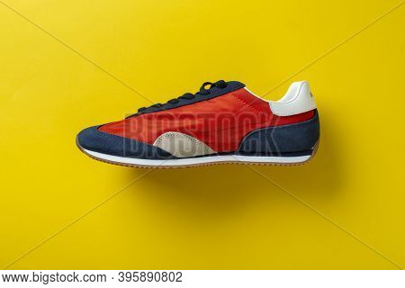 New Sneaker On A Yellow Background. Lifestyle Sneaker Sport Shoe. Top View.