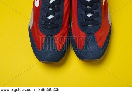 Pair Of New Youth Sneakers On A Yellow Background.  Lifestyle Sneaker Sport Shoe.