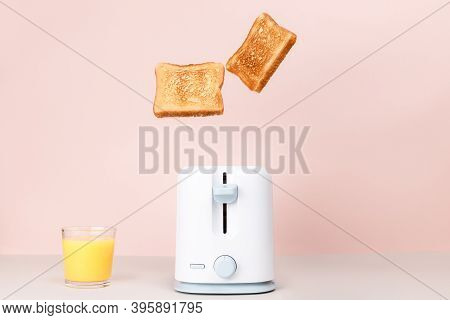 Toasted Bread Flew Out Of White Toaster. Near Glass Of Orange Juice. Levitation Food. Flat Lay. Deli