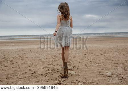 Unrecognizable Pretty Girl In Grey Dress Runs Across The Sand To The Sea. The View From The Back. A