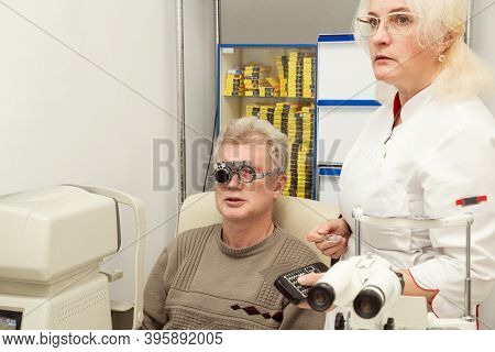 Woman Doctor Ophthalmologist Checks The Vision Of A Man In A Medical Office. Doctor And Patient In A