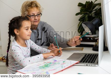 Cute And Happy Little Girl Child Using Laptop Computer With Her Grandma, Studying Through Online E-l