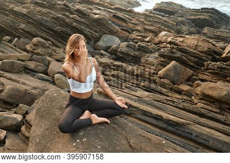 Woman Practicing Yoga In The Nature. Meditating Outdoors