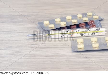 Cold Thermometer Pills. Flu Cure, Remedy For Convalescence. Photo On A Wooden Background