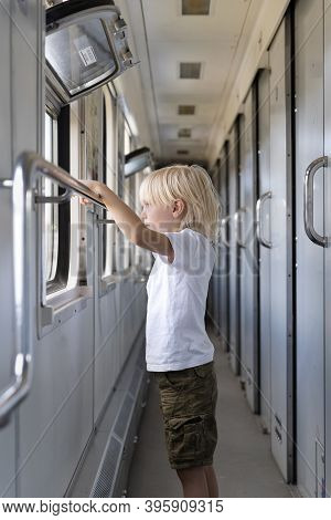 Blond Boy With Interest Looks In The Window Of The Train. Traveling With Children.